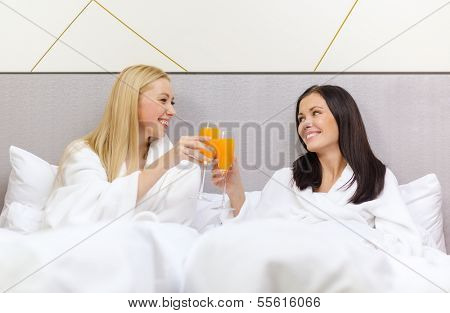 hotel, travel, friendship and happiness concept - smiling girlfriends having breakfast in bed