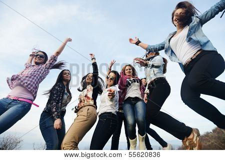 Happy teen girls having good fun time outdoors jumping on green meadow