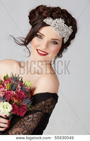 Beautiful brunette young bride with braided hair with shiny crown wearing black lace dress in studio