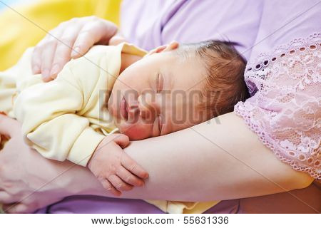 newborn baby sleeping on mother hands