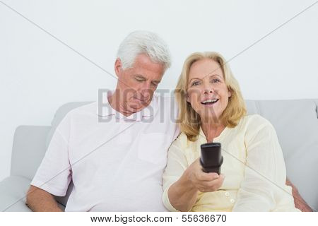 Relaxed senior couple watching television in a house