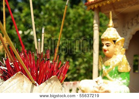 Red Incense Sticks In Front Of A Buddhist Statue