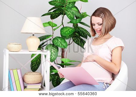Young regnant woman sitting on armchair and reading book at home