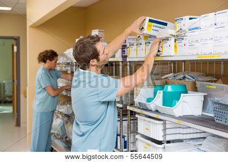 Nurses arranging stock in hospital storage room