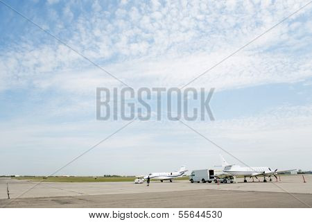 Private jets on airfield against cloudy sky