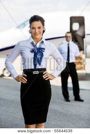 Portrait of confident airhostess with hands on hip against pilot and private jet at airport terminal