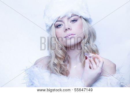 Portrait in cool winter tones of a beautiful young woman with long blond hair dressed in elegant white fluffy winter fashion with a hat and off the shoulder top