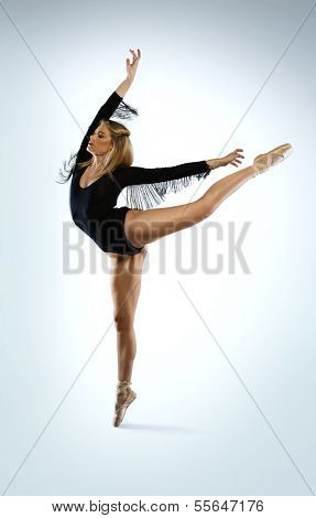 Beautiful graceful ballet dancer doing an arabesque en pointe with her arms outspread in an elegant pose