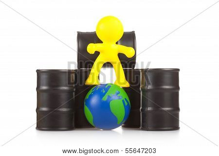 Toy  Little Man Sits Next On Butts To Oil The Globe. The World Supremacy Concept Oil-extracting The