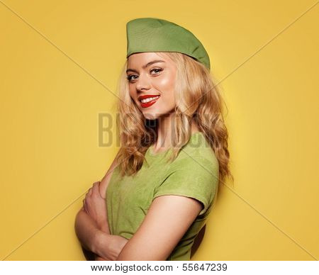 Beautiful glamorous blond woman in a trendy green summer ensemble standing with folded arms and a jaunty expression on yellow