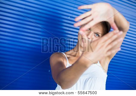 Pretty, young woman making a photo composing/shooting gesture with her hands