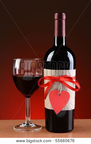Closeup of a wine bottle decorated for Valentines Day. A glass of wine is next to the bottle. The bottle has a red ribbon and heart shaped tag and a blank label.
