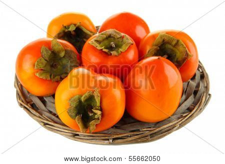 Ripe persimmons on wicker stand isolated on white