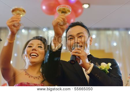 Natural candid photo Asian Chinese wedding dinner reception, bride and groom champagne toasting.