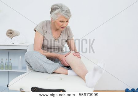 Senior woman with her hands on a painful knee while sitting on examination table