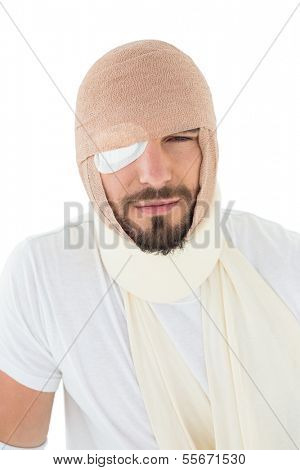 Close-up portrait of a young man with head tied up in bandage over  white background
