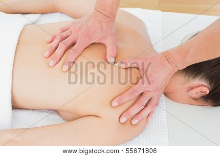 Close-up of male physiotherapist massaging woman's back in the medical office