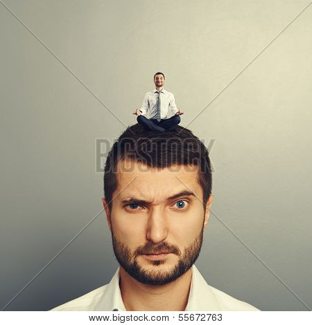 small happy man sitting on the head big dissatisfied man