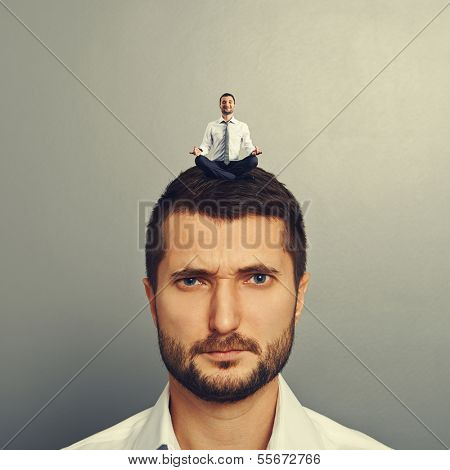 displeased man with small happy man on the head