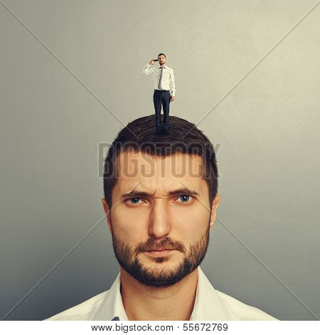 sullen man with small man on the head over grey background