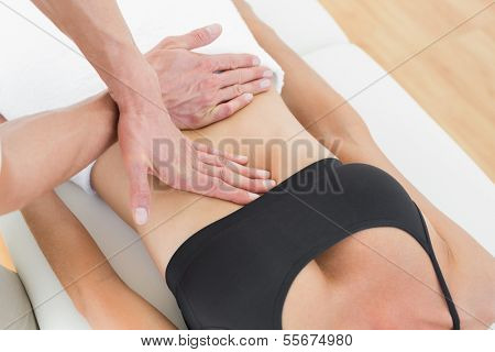 Close-up mid section of a physiotherapist massaging woman's body in the medical office