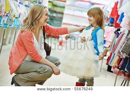 woman and little girl choosing and trying on clothes during shopping at garment supermarket