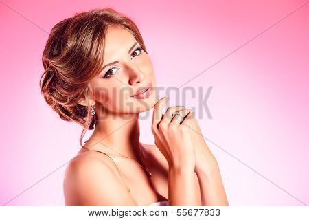 Beautiful young woman smiling at camera over pink background.
