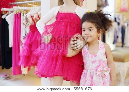 Little pretty girl holds hand of dummy and looks away in children store.