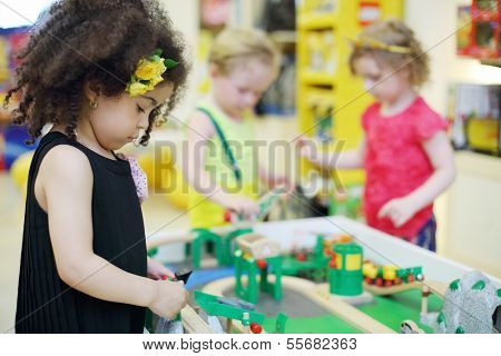 Two little girl and boy play with toy railroad in children store. Focus on left girl.