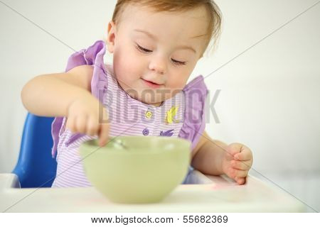 Little smiling baby sits at highchair and eats porridge on plate. Shallow depth of field.
