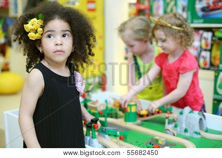 Little girl looks up and two children play with toy railroad in store. Focus on left girl.