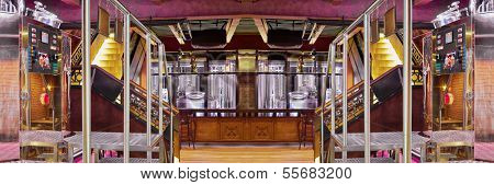 Hall in cafe with metal ladder, brewery tank and control board of microbrewery