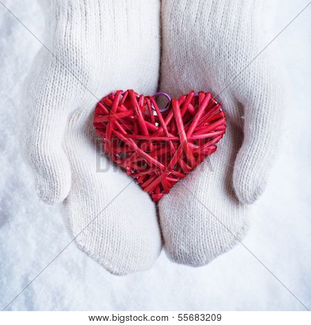 Female hands in white knitted mittens with a entwined vintage romantic red heart on a snow background. Love and St. Valentine concept.