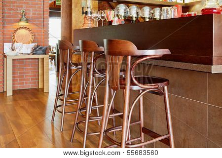 Three tall wooden stools at counter with beverages and glasses in cafe
