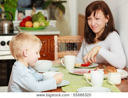 Family Eating Corn Flakes And Bread Breakfast Meal At The Table