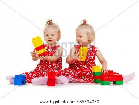 children and twins concept - two identical twin girls in red dresses playing with toy blocks