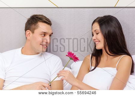 hotel, travel, relationships, holidays and happiness concept - smiling couple in bed with pink flower