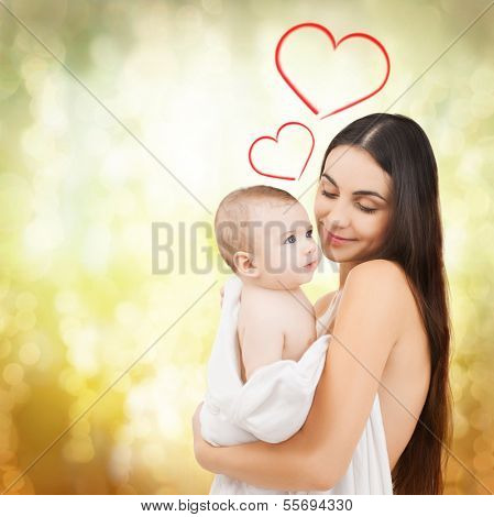 family, children, parenthood and happiness concept - happy mother feeding her adorable baby