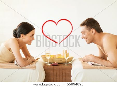 spa, beauty, love and happiness concept - smiling couple with candles in spa salon drinking champagne