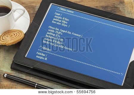 designing webpage format - CSS style sheet code on a digital tablet with a cup of coffee