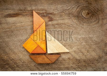 abstract picture of a sailing yacht built from seven tangram wooden pieces over a rustic  barn wood, artwork created by the photographer