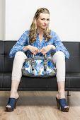 stock photo of clog  - woman wearing denim clogs with a handbag sitting on sofa - JPG