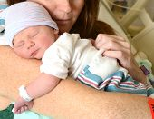 stock photo of snuggle  - new mother holding a sleeping newborn infant in hospital - JPG