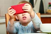 foto of toy phone  - Funny dirty boy child kid taking photo with red mobile phone indoor - JPG