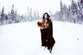 foto of witch ball  - Witch or woman in black cloak with fire ball in white snow forest - JPG