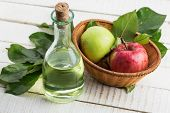 stock photo of cider apples  - Apple vinegar and apples on white wooden table - JPG