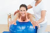 stock photo of chiropractic  - Physical therapist assisting young woman with yoga ball in the gym at hospital - JPG