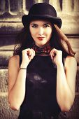 stock photo of bowler  - Beautiful brunette in bowler hat and bow - JPG