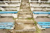 picture of grandstand  - Old dirty destroyed blue grandstands and stairs at old stadium - JPG