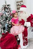 picture of saint-nicolas  - little girl in a beautiful dress sits on a lap at Saint Nicolas about a New Year tree - JPG